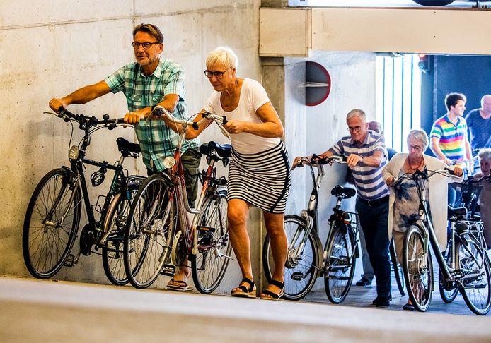 Mensen moet met fiets steile helling op bij gebrek aan berging op begane grond.
