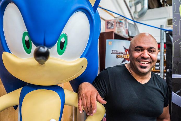 De Haagse ondernemer Hasan Tasdemir staat glunderend naast een levensgroot beeld van de wereldberoemde gamefiguur Sonic the Hedgehog.
