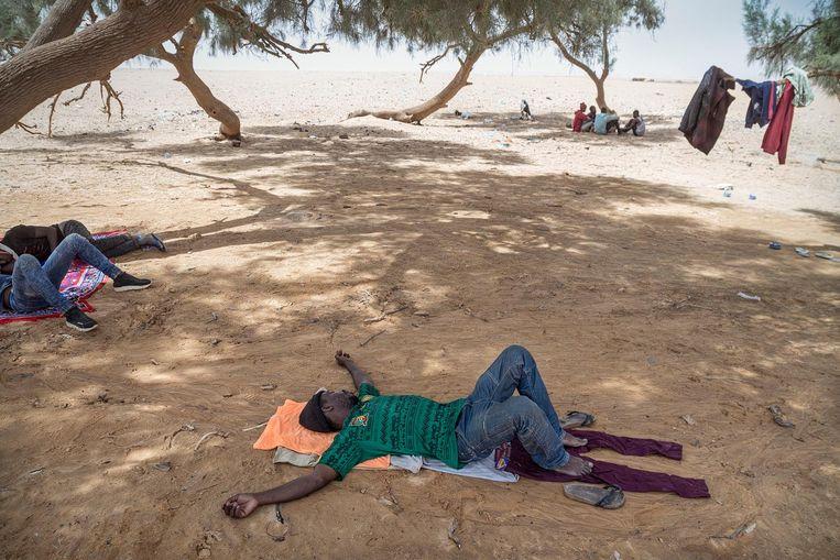 Gestrande migranten rusten uit in de schaduw. Beeld Sven Torfinn