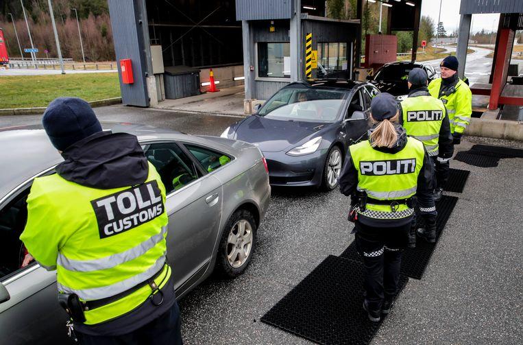 Grenscontrole tussen Zweden en Noorwegen. Er zijn extra agenten aangesteld om het nieuwe coronabeleid te handhaven. Beeld AP