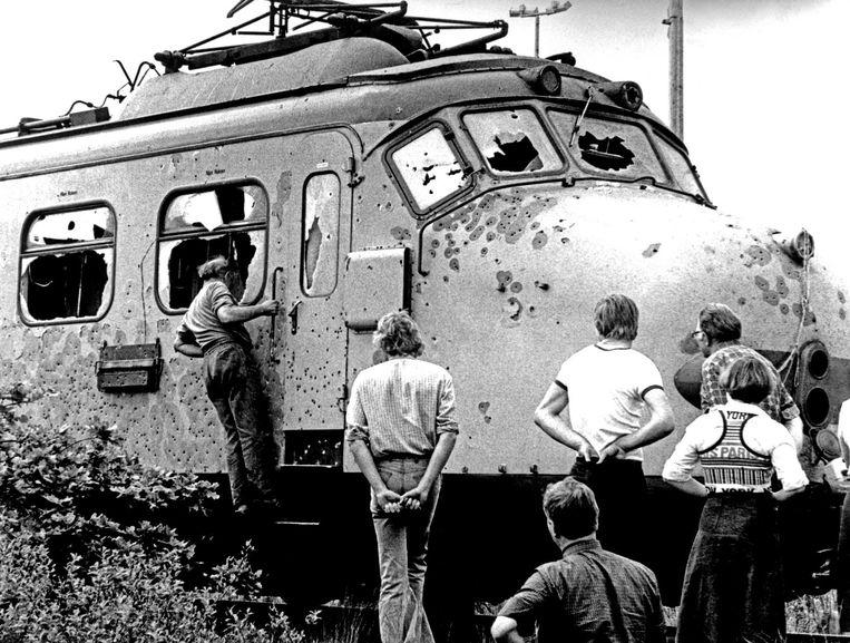 Nieuwsgierigen inspecteren de verwoeste trein na de bevrijdingsactie. Beeld null