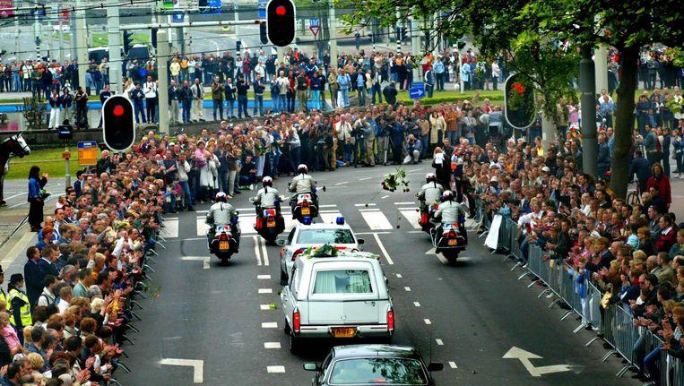 Mensen applaudisseren als de stoet met de lijkwagen met het stoffelijk overschot van Pim Fortuyn in Rotterdam passeert, op weg naar de kathedraal waar de uitvaartdienst wordt gehouden. Beeld anp