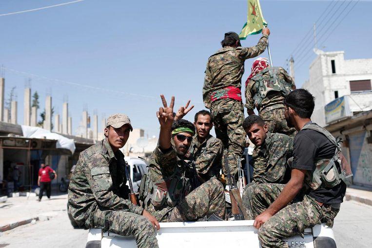 YPG-strijders vieren de inname van een stadje in de buurt van Raqqa in 2015. De hoofdstad van het IS-kalifaat is nu omsingeld en klaar om aangevallen te worden. Beeld epa