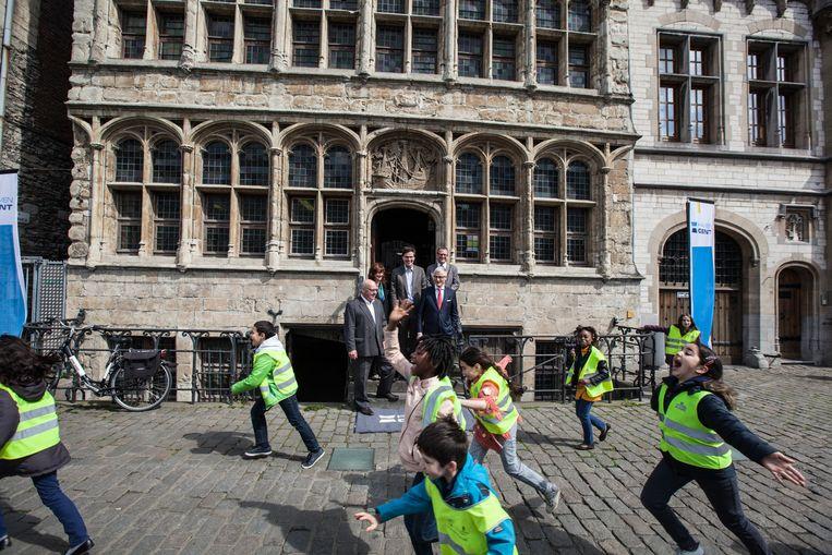 Terwijl minister Bourgeois en de delegatie voor het Havenhuis poseren, lopen kinderen voor de camera.