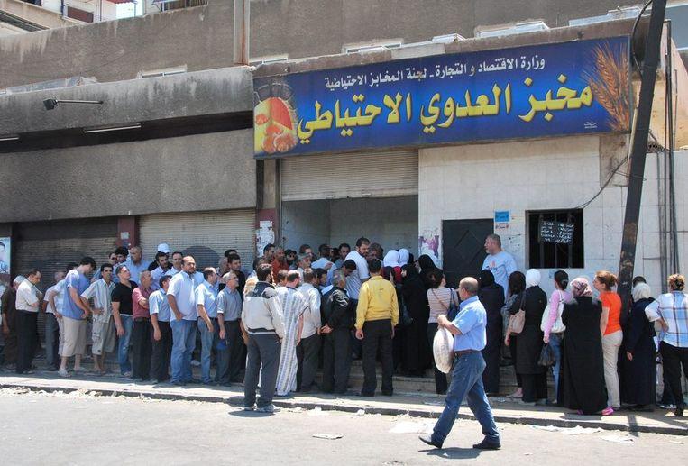 Inwoners van Damascus staan in de rij bij een bakker Beeld afp