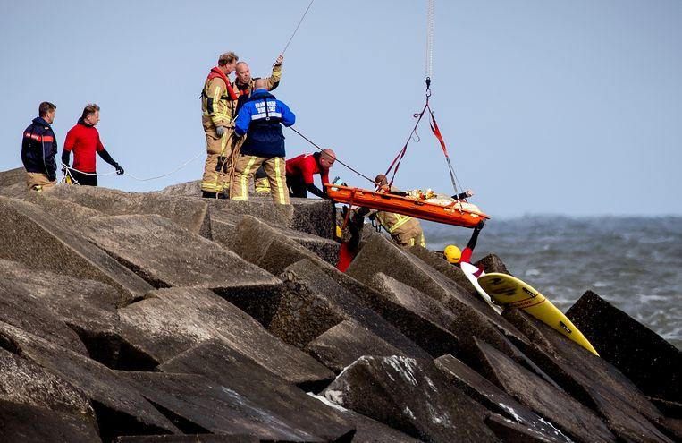 Hulpverleners bergen een van de lichamen van de jongens.  Beeld ANP