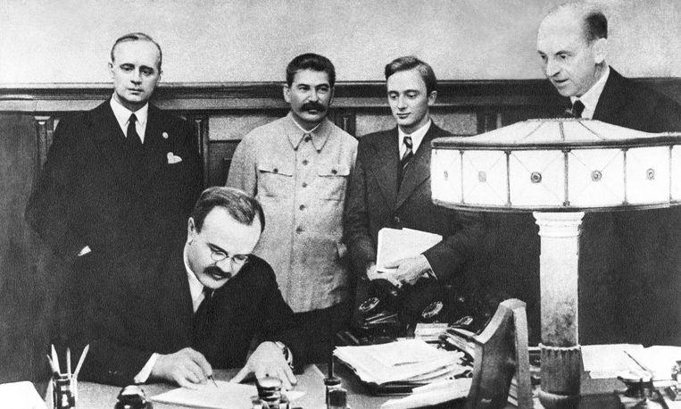 Sovjet-minister Molotov zet zijn handtekening onder het niet-aanvalspact, met achter zich de Duitse minister Von Ribbentrop en Stalin.  Beeld TASS via Getty Images