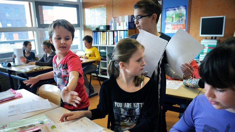 Klassikaal onderwijs aan groep 7 van een basisschool. Beeld Marcel van den Bergh / de Volkskrant
