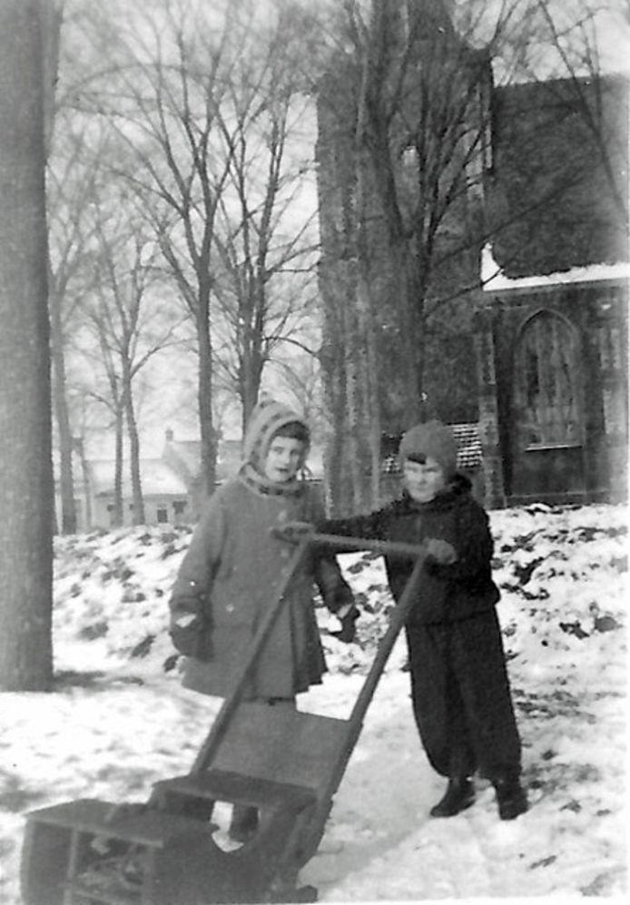 Leni Schaleven en haar broertje Rien bij de kerk in Renesse. Op de achtergrond is de wal van de loopgraaf zichtbaar.