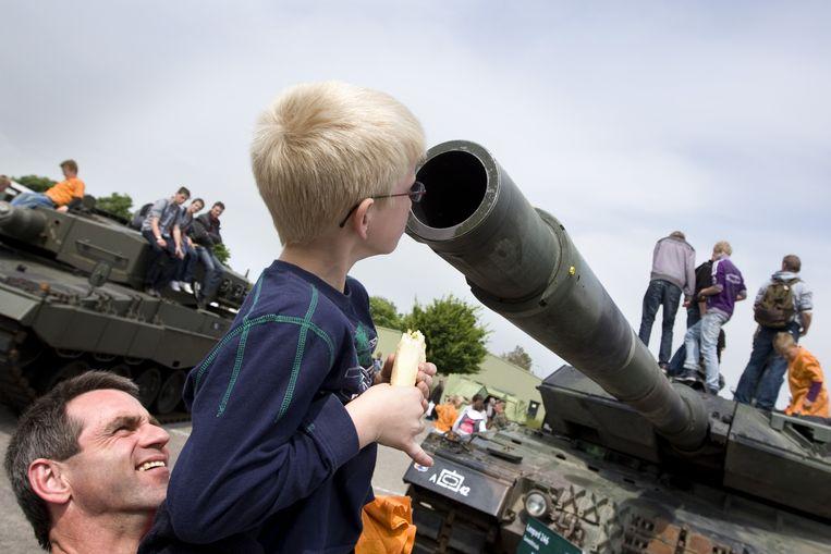 Een vader tilt zijn zoon op om een blik te werpen in de loop van een Leopard tank tijdens de landmachtdagen in 2010 op de Johannes Postkazerne in Havelte. Beeld ANP