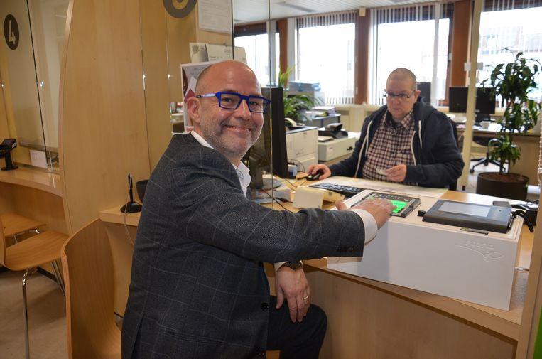 Burgemeester Jo Fonck krijgt zijn nieuwe elektronische identiteitskaart met vingerafdruk aan het loket in Denderleeuw.