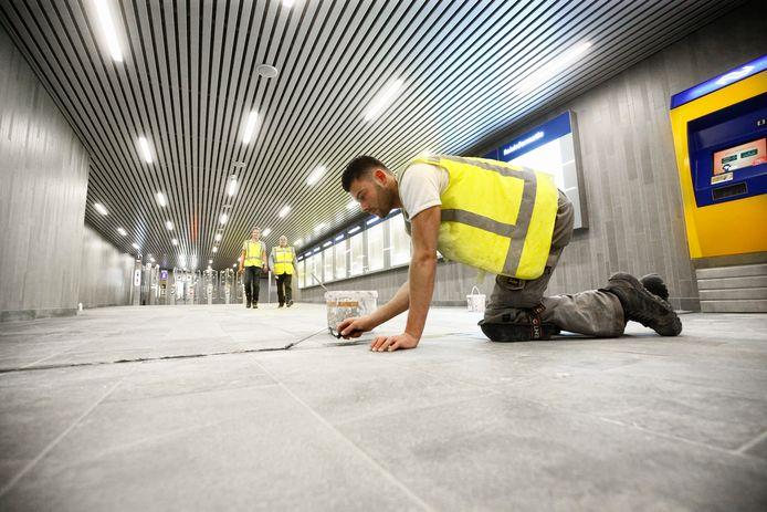 Bouwvakkers verrichten de laatste kitwerkzaamheden aan de Middentunnel die maandag weer opengaat voor publiek.