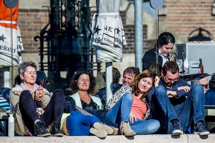 Mensen bij Hotel New York in de lentezon