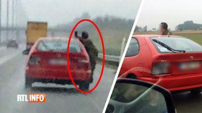 Levensgevaarlijke toestanden op E411: man in militair uniform hangt uit rijdende auto om zich te filmen