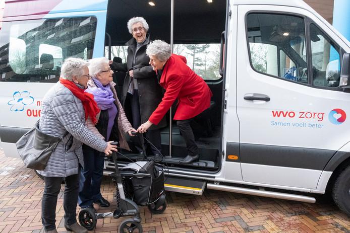Lia Lous (links, rode sjaal) en Lia Maljers (rechts, rode jas) helpen Nel van Wijk (met rollator en paarse sjaal) de 'Samen-op-stap-bus' in. Joke van Es (lange groene jas) staat al in de bus.