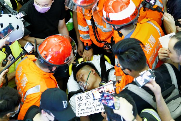 Un homme blessé à l'aéroport de Hong Kong est soigné par des secouristes. Certains manifestants l'accusent d'être un policier chinois en civil