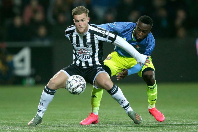 Heracles-aanvaller Joey Konings schermt de bal af tegen Feyenoord.