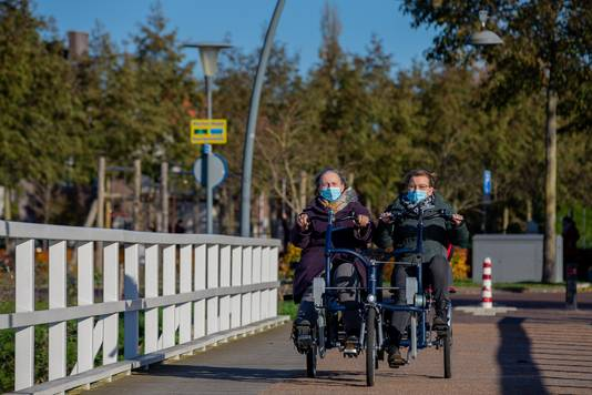 Met de duofiets de brug over en de wijk uit. Foto: David van Haren.