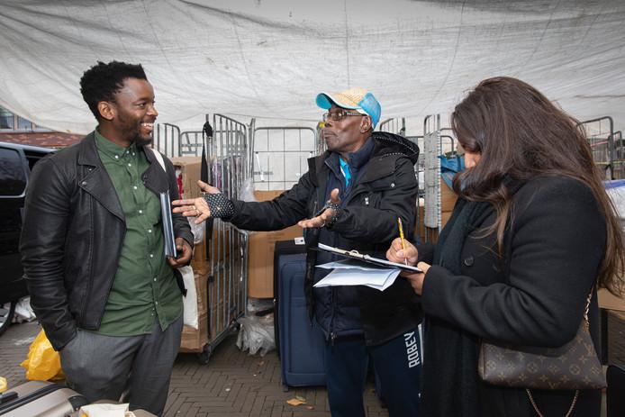 Marktkoopman Stanly Chocolaad in gesprek met de Zuid-Afrikaanse kunstenaar Mohau Modisakeng.