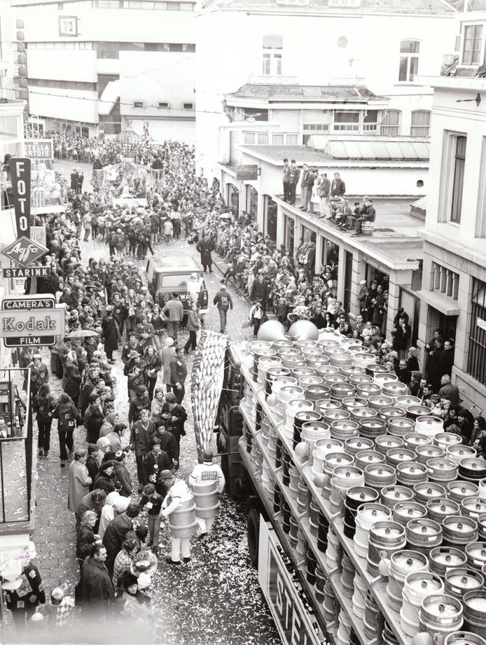 Carnavalsoptocht in Lampegat, eerste helft van de jaren zeventig. Zelfs vanaf het dak van de voormalige tapijthandel Lebesque werd naar de optocht gekeken. Bierbrouwerijen deden ook toen goede zaken, getuige de reclamewagen van Stella Artois.