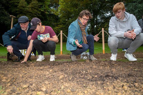 Kurt Moens (N-VA) en Riet Gillis (Groen) helpen de laatste bloembollen planten.