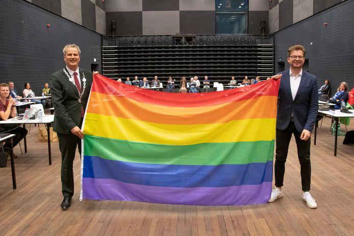 Burgemeester Evert Weys (l) en Tycho Holleman (VVD) poseren met de regenboogvlag tijdens de gemeenteraad. Zie kader verderop in de tekst.