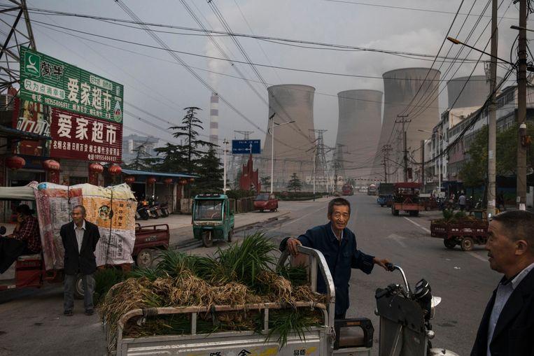 Chinese kooplieden op staat in Huainan in de oostelijke provincie Anhui. Op de achtergrond staat een grote kolencentrale. Beeld Getty Images
