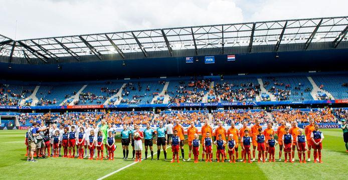 Nederland en Nieuw-Zeeland luisteren naar hun volkslied voorafgaand aan de wedstrijd, die eindigt in een 1-0 overwinning voor Nederland. Op de achtergrond een halfleeg stadion.