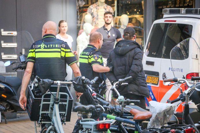 De politie voert een van de verdachten af.
