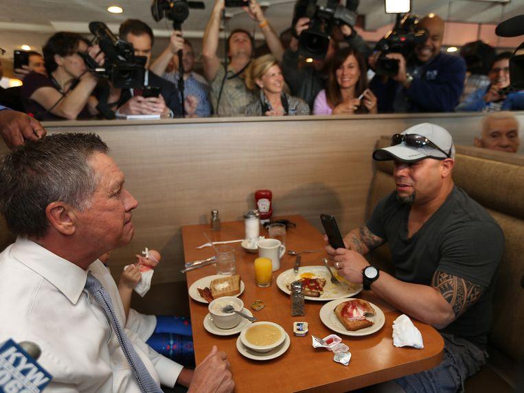 Gouverneur John Kasich praat in de Penrose Diner in Philadelphia met bezoeker John Antipuna. Kasich, die tot nu toe slechts één staat heeft gewonnen, hoopt een kans te maken op een contested convention in juli. Ook wordt hij veel genoemd als potentiële running mate van Donald Trump. Beeld AP