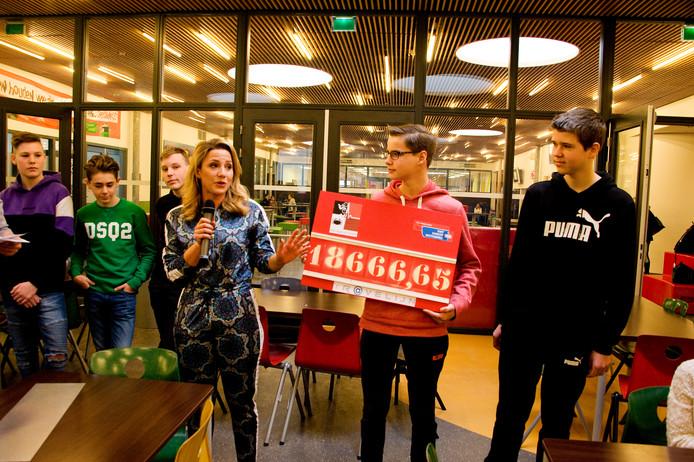 De leerlingen overhandigen de cheque aan Fien Vermeulen