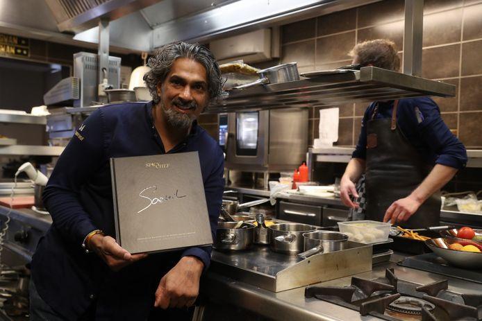 Soenil Bahadoer met zijn recepten- en verhalenboek