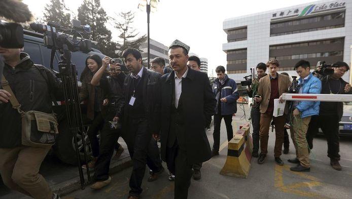 Een familielid van Maimaitijiang Abula staat met mensen van de media voor een hotel in Beijing