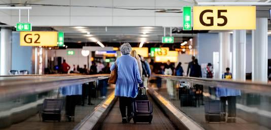Reizigers bij de gates op luchthaven Schiphol.