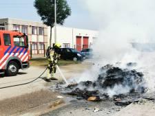 Vuilniswagen stort brandende lading op straat: brandweer blust de boel