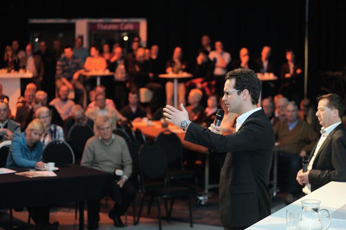 Wethouder Jean-Pierre Schouw probeert de zaal ervan te overtuigen dat de gemeente de arbeidsmigranten wel zal moeten huisvesten. foto Peter van Trijen/het fotoburo