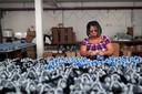 Een medewerker trekt strepen op beschermende gezichtsmaskers in de Destra Brasil-fabriek, die kampt met materiaaltekort vanwege de grote vraag na de uitbraak van het coronavirus, in Sao Paulo.