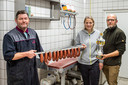 Simone en Bram van Risp van Het Wildhuys uit Berkenwoude met de bekroonde rookworst van ganzenvlees. Links ambachtelijke slager Martin Meijer uit Lekkerkerk die de worsten bereidt en rookt in zijn worstmakerij.