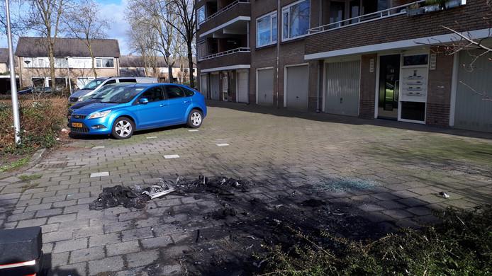 Zwartgeblakerde resten van uitgebrande auto op parkeerterrein naast een van de vier flats aan J.J. Van Deinselaan in Enschede.