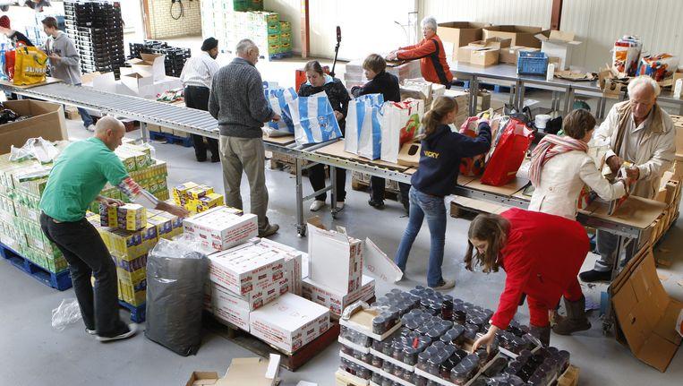 Vrijwilligers van de Voedselbank in Den Haag stellen de voedselpakketten samen. Beeld ANP