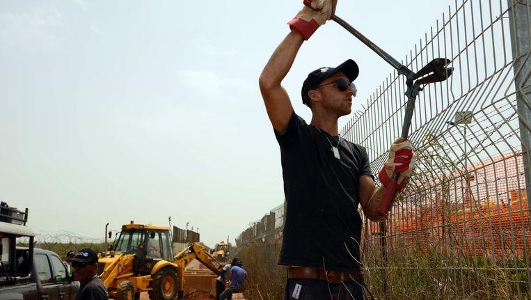 Een Israëlische arbeider werkt aan een hek op de grens van Israël en Libanon. Beeld AFP