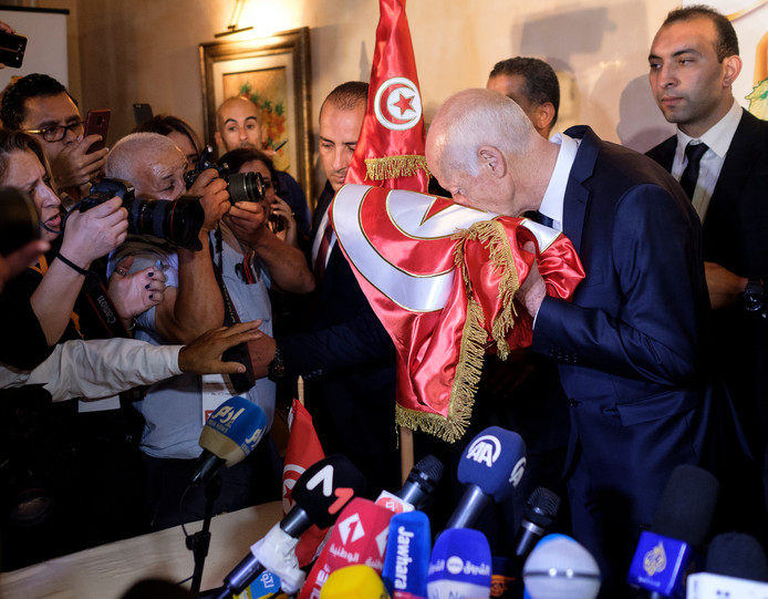 Kaïs Saïed kust de Tunesische vlag na het bekend worden van de eerste exitpolls van de presidentsverkiezingen.