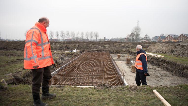 Projectleider en initiatiefnemer Sjaak de Ligt (r) en een controleur bij het fundament waar straks het monument op zal worden geplaatst Beeld Marijke Stroucken