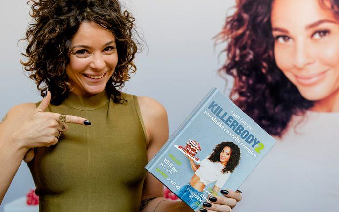 Fajah Lourens met Killerbody 2, een boek met sport- en dieettips.