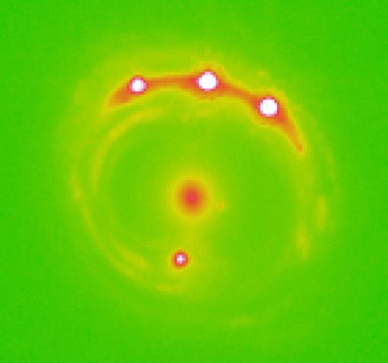 De gravitationele lens RX J1131-1231 is te zien in het midden, met vier