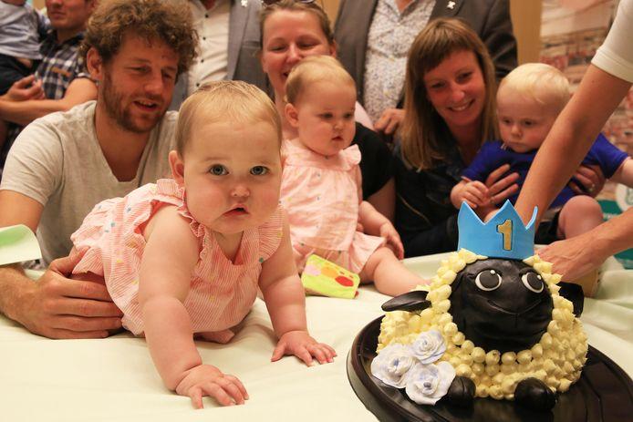 De kinderen vieren hun eerste verjaardag met taart.