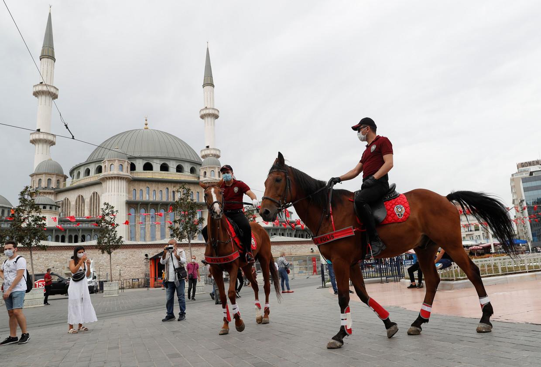 Turkse politieagenten te paard controleren op het Taksimplein in Istanbul op het dragen van een mondkapje.  Beeld REUTERS