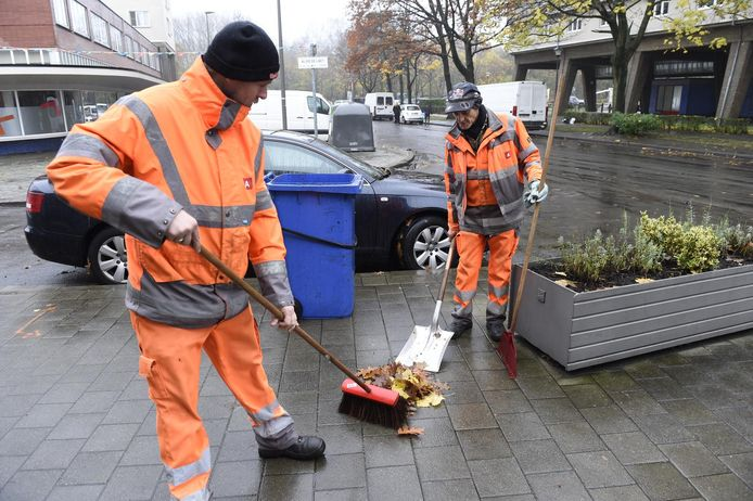 Twee stadsarbeiders vegen bladeren bij elkaar.