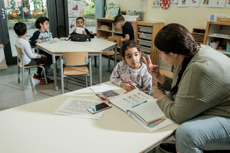 Een juf neemt het huiswerk door met een kind op basisschool De Toekomst. Beeld Jakob van Vliet