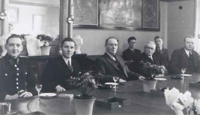 Burgemeester Bisschop (tweede van links) in de raadszaal van 's-Gravenzande. Later werd hij benoemd in Naaldwijk.